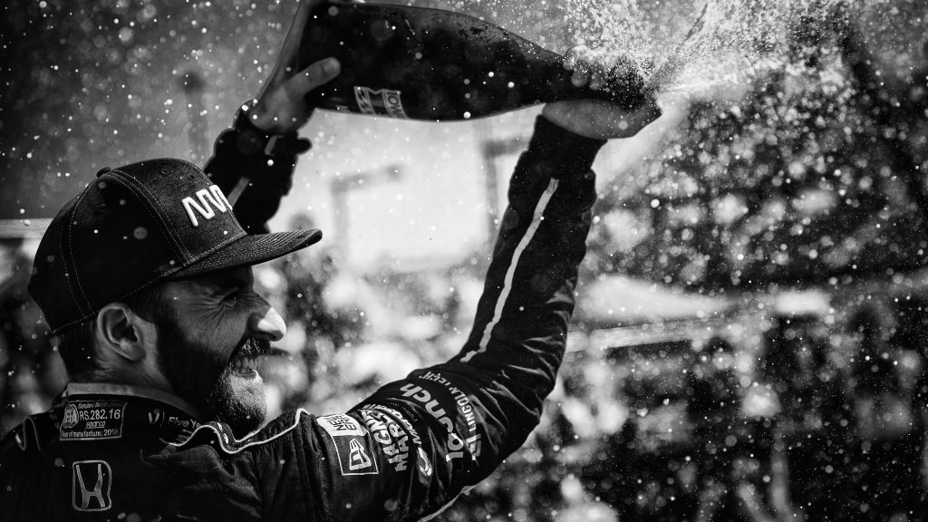 James Hinchcliffe sprays the champagne in Victory Circle after winning the Iowa Corn 300 at Iowa Speedway -- Photo by: Shawn Gritzmacher